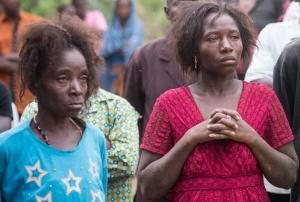 The faces say it all - grief at the loss of a loved one clutched away by the cold hands of the deadly ebola virus.
