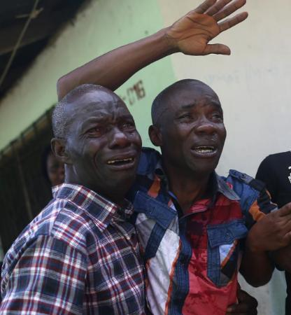 The devastating effect of the disease. Men in tears in Liberia as the Ebola Virus Disease takes its toll.