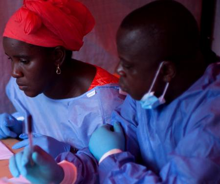Nene Aminata Diallo and Gamou Saiman Gaston, from the WHO Ebola vaccination team, carefully go through the consent process with a participant in the Ebola vaccine trial. Obtaining clear consent from participants, that this is a trial, that there are no guarantees, that there may be unexpected consequences from the vaccine, is important in the trial process.