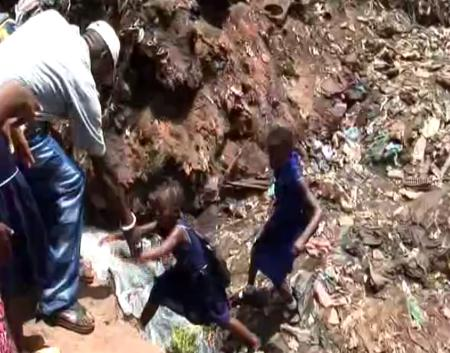 School children are helped across a stream as they move through a pile of garbage.