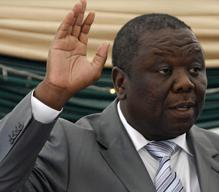 New Zimbabwean PM raises his hands as he takes the oath of office
